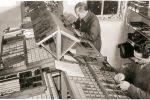 Rechts Gijs Veerman in de jaren '60, bezig met het handmatig zetten van drukwerk m.b.v. de letterkast.